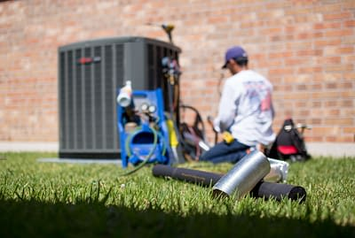 HVAC technician working on air conditioning unit next to red brick building home