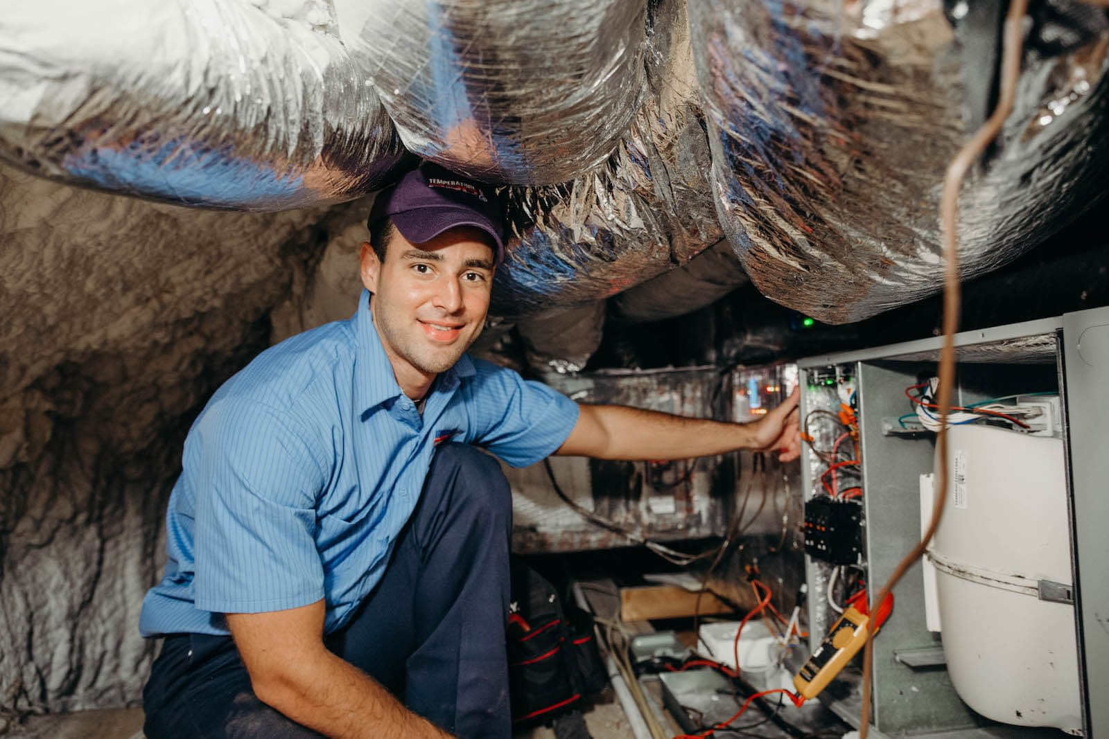 hvac technician inspecting a furnace